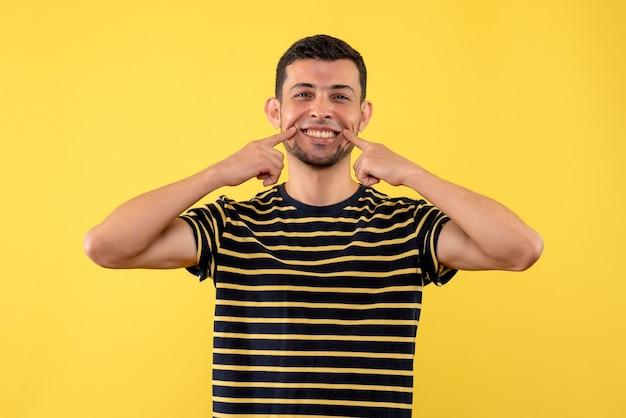 黄色の孤立した背景に彼の笑顔を指している黒と白の縞模様のtシャツの正面図若い男性