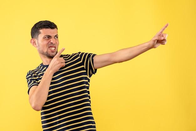 黄色の孤立した背景に右を指している黒と白の縞模様のtシャツの正面図若い男性