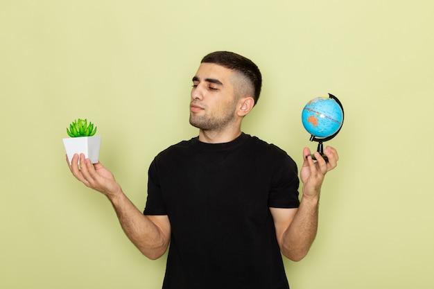 緑の小さな緑の植物と小さな地球を保持している黒のtシャツで正面の若い男性