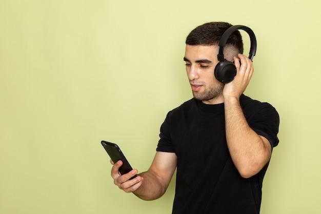 전화를 들고 녹색 음악을 듣고 검은 티셔츠에 전면보기 젊은 남성