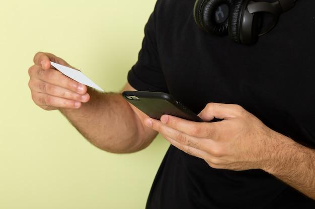 Вид спереди молодой мужчина в черной футболке держит белую карточку и разговаривает по телефону на зеленом