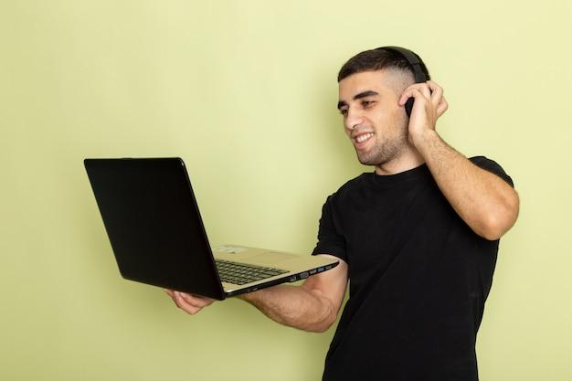 녹색에서 음악을 듣는 동안 웃 고 노트북을 사용하는 검은 티셔츠에 전면보기 젊은 남성