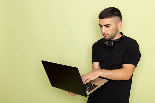 緑のラップトップを使用して黒のtシャツで正面の若い男性