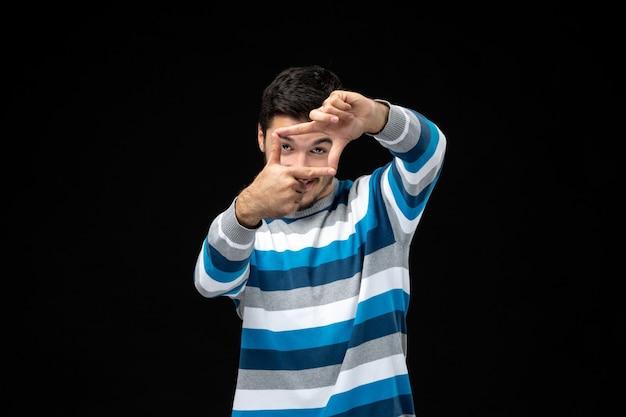 Вид спереди молодой самец в синей полосатой майке делает жест кадра руками