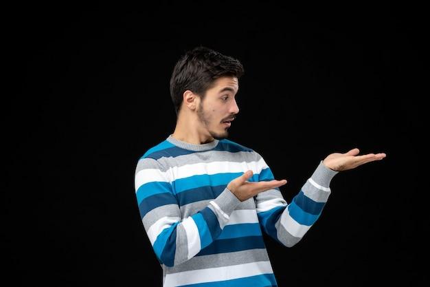 검은 벽 사진 색상 감정 모델 어둠 남자에 파란색 줄무늬 저지에 전면 보기 젊은 남성