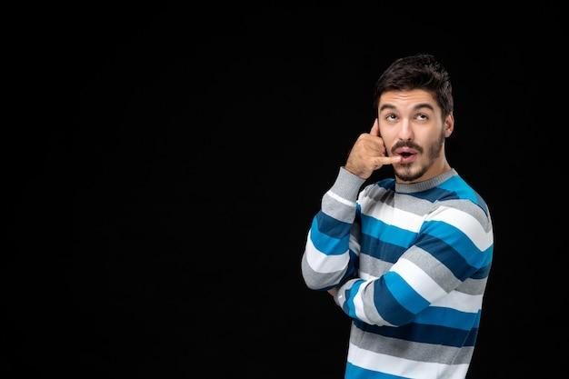 黒い壁に青い縞模様のジャージの正面図若い男性