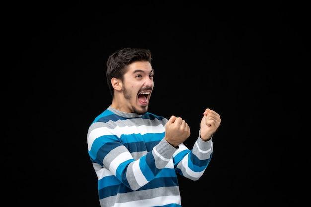 파란색 줄무늬 저지를 입고 검은 벽에 감정적으로 기뻐하는 전면 보기 젊은 남성