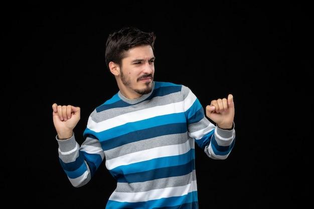 검은 벽에 기뻐하는 파란색 줄무늬 저지를 입은 전면 보기 젊은 남성