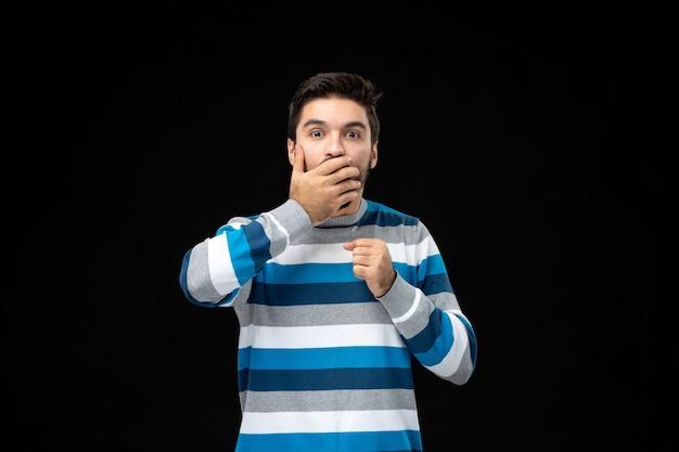 파란색 줄무늬 저지를 입은 전면 보기 젊은 남성은 검은 벽에 충격을 받았습니다.