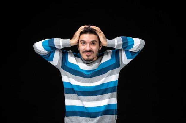 검은색 벽에 웃고 있는 파란색 줄무늬 저지를 입은 전면 보기 젊은 남성