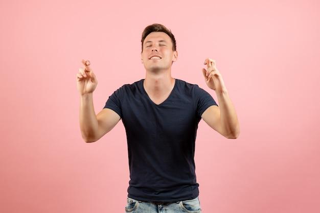분홍색 배경에 닫힌 눈을 가진 그의 손가락을 건너 파란색 티셔츠에 전면보기 젊은 남성 남성 감정 컬러 모델 인간