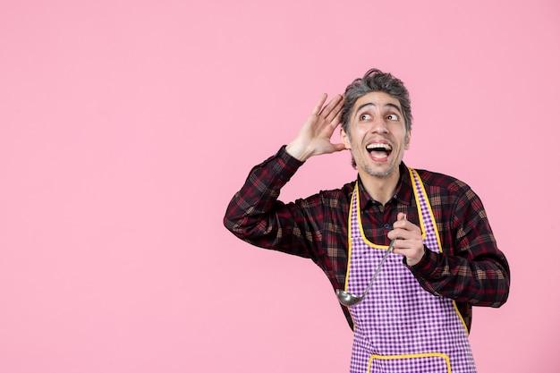 전면 보기 분홍색 배경에 수프 숟가락을 들고 케이프에 젊은 남성 직업 수평 작업자 음식 남편 부엌 요리사 색상