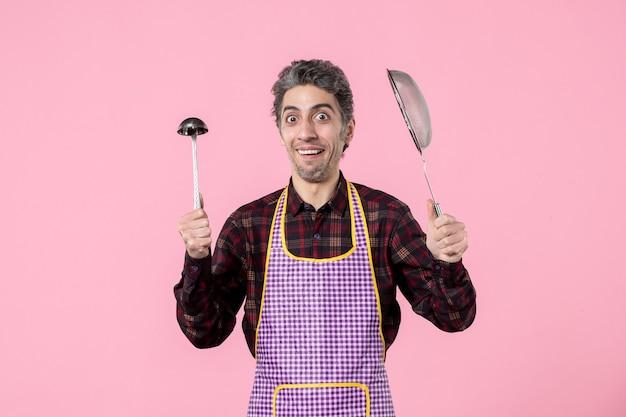 Вид спереди молодой мужчина в накидке с ситом и ложкой на розовом фоне горизонтальный профессия муж униформа кухня кухня повар