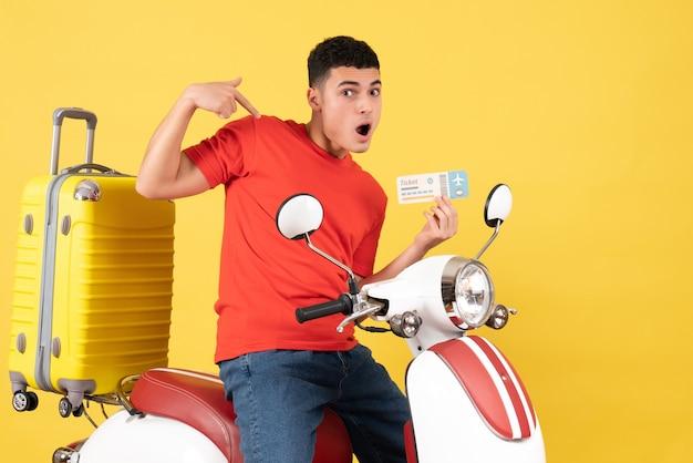 Вид спереди молодой мужчина в повседневной одежде на мопеде с билетом, указывая на себя