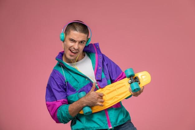 音楽を聴くとピンクの机の上にスケートボードを保持しているカラフルなコートの正面の若い男性