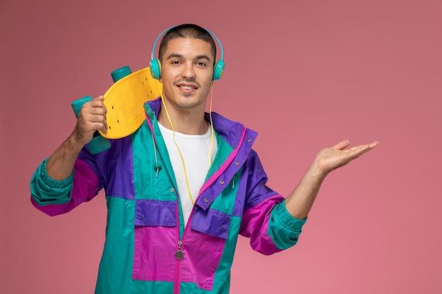 ピンクのデスクの男性にスケートボードを保持している音楽を聴くカラフルなコートを正面から見た若い男性