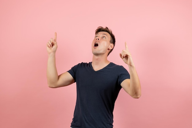 明るいピンクの背景にポーズをとって紺色のtシャツの正面図若い男性