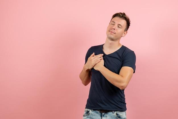ピンクの背景にポーズをとって紺色のtシャツの正面図若い男性