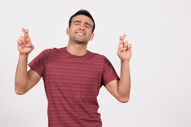 正面図白い背景の上の彼の指を交差させる暗赤色のtシャツの若い男性