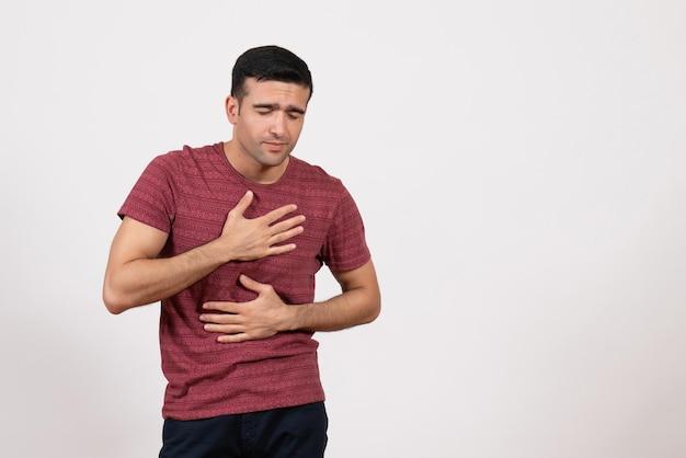 正面図白い背景に息の問題を抱えている暗赤色のtシャツの若い男性