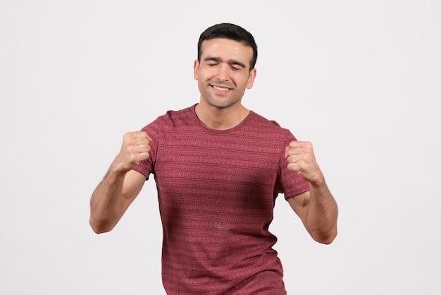 正面図白地にポーズと歓喜の濃い赤のtシャツの若い男性