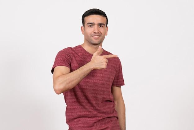 明るい白の背景にポーズをとって濃い赤のtシャツの正面図若い男性