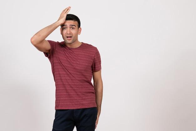 正面図白地にポーズをとって濃い赤のtシャツの若い男性