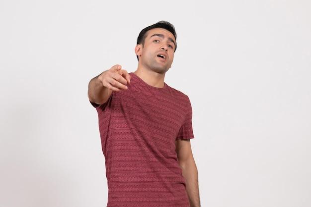 正面図白地に立って指摘している暗赤色のtシャツの若い男性