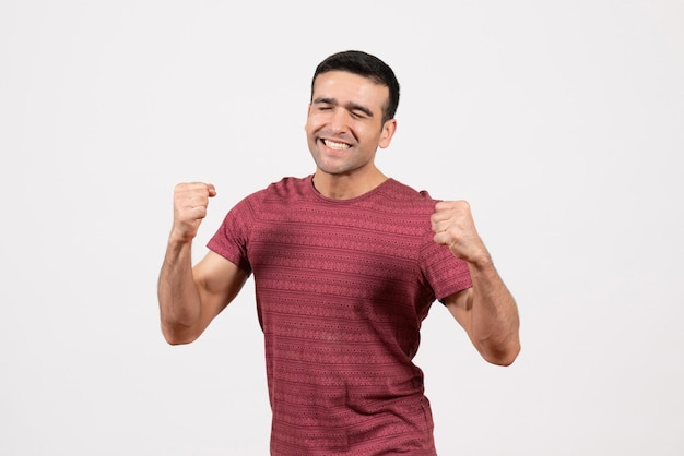 흰색 배경에 서서 기뻐하는 짙은 빨간색 티셔츠를 입은 전면 보기 젊은 남성
