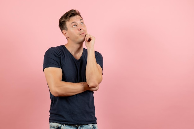 ピンクの背景でポーズと思考の暗いtシャツの正面図若い男性