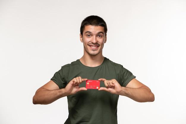 白い壁のフィルム孤独な映画の銀行カードを保持している緑のtシャツの正面図若い男性
