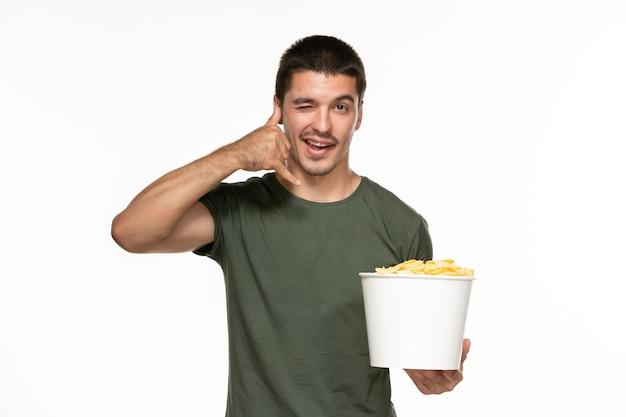 白い壁にジャガイモのcipsが付いているバスケットを保持している緑のtシャツの正面図若い男性孤独な楽しみ映画映画シネマ