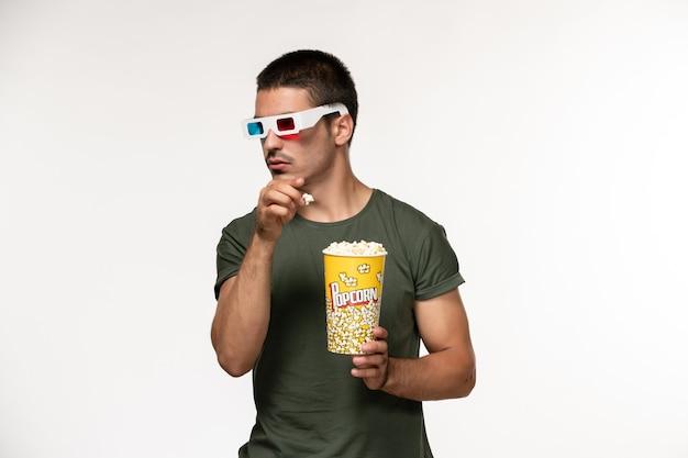 ライトホワイトの壁のフィルム孤独な映画の男性の映画にdサングラスでポップコーンを保持している緑のtシャツの正面図若い男性