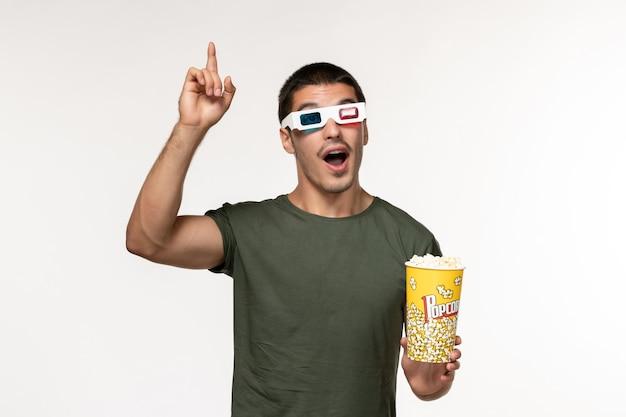 Вид спереди молодой мужчина в зеленой футболке, держащий попкорн в солнцезащитных очках d, смотрит фильм на белой стене, фильм одинокий кинотеатр мужской фильм