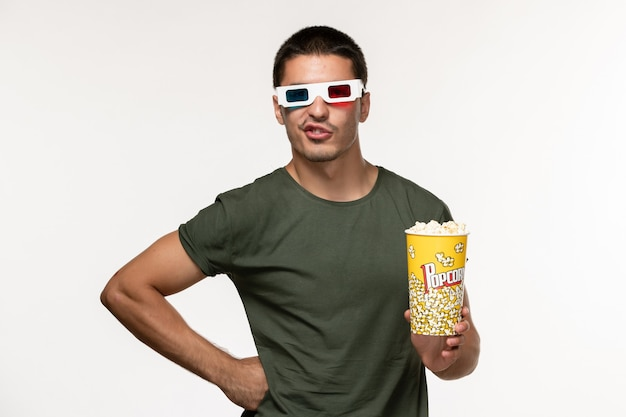 白い壁のフィルム孤独な映画の男性映画にdサングラスでポップコーンパッケージを保持している緑のtシャツの正面図若い男性