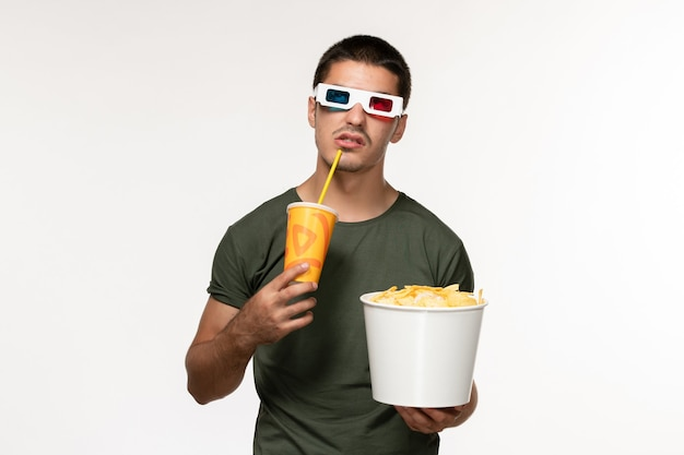 正面図緑のtシャツを着た若い男性がジャガイモのcipsを保持し、白い壁のフィルムの男性の孤独な映画にdサングラスでソーダを飲む