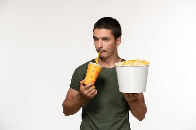 ジャガイモのcipsを保持し、白い壁のフィルムシネマ男性孤独な映画でソーダを飲む緑のtシャツの正面図若い男性