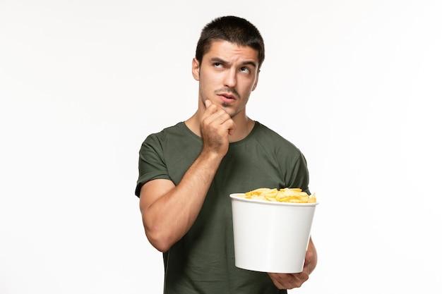 Вид спереди молодой мужчина в зеленой футболке, держащий картофельные чипсы и смотрящий фильм, думающий на белой стене, одинокий фильм, кино