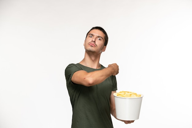 밝은 흰색 책상 외로운 영화 영화 영화 사람에 감자 cps를 들고 녹색 티셔츠에 전면보기 젊은 남성