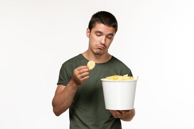 감자 cips와 흰 벽 사람 외로운 영화 영화 영화에 먹는 녹색 티셔츠에 전면보기 젊은 남성