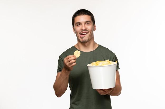 감자 cips와 흰 벽에 먹는 녹색 티셔츠에 전면보기 젊은 남성 사람 외로운 영화 영화 영화