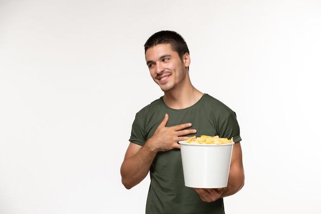 Вид спереди молодой мужчина в зеленой футболке с картофельными чипсами и улыбающийся на белой стене фильм человек мужчина одинокий кино