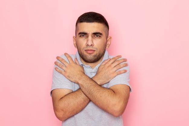 ピンクの寒さから震えながら灰色のシャツで正面の若い男性
