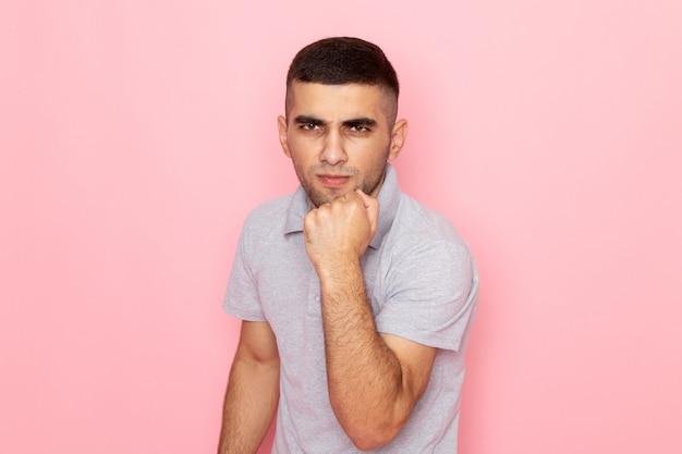 ピンクの拳で彼の喜びを示す灰色のシャツの正面の若い男性