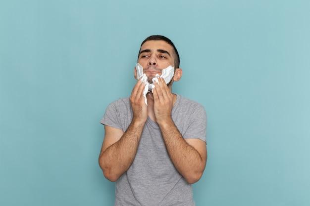正面図灰色のtシャツを着た若い男性が、アイスブルーの壁にひげを剃るために白い泡で顔を覆っているひげの泡の髪のかみそりのひげそり
