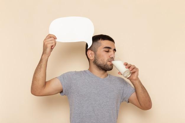 Вид спереди молодой мужчина в серой футболке пьет молоко и держит белый знак на бежевом