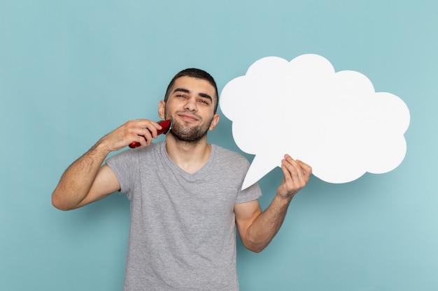 大きな白い看板と氷の青い壁に電気かみそりを保持している灰色のtシャツの正面図若い男性ひげ泡髪かみそり剃