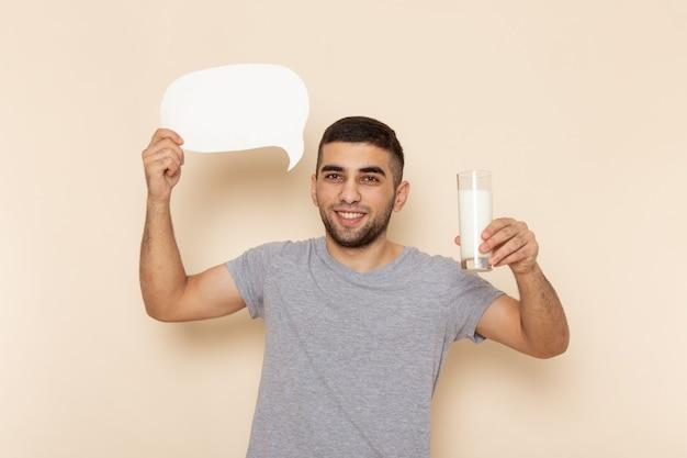 Вид спереди молодой мужчина в серой футболке, держащий стакан молока и белый знак на бежевом