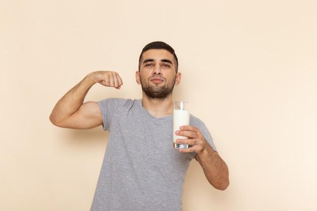 Вид спереди молодого мужчины в серой футболке, держащего стакан молока на бежевом
