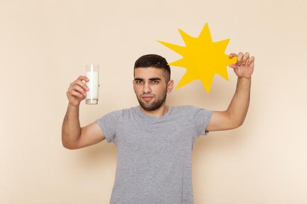Вид спереди молодой мужчина в серой футболке держит стакан молочно-желтый знак на бежевом